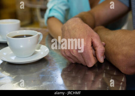Portrait de couple holding hands at table in cafe Banque D'Images