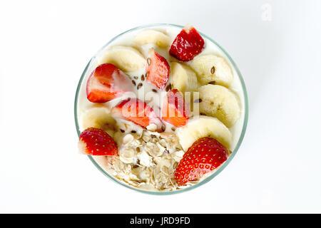 Yogourt maison blanche avec des flocons d'avoine fraise et banane et graines de lin dans un bécher en verre sur Banque D'Images