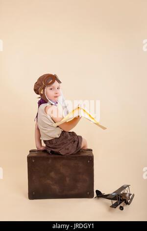 Jeune fille jouant avec vintage papier avion sur vieille valise. Isolé sur fond dégradé. Rêves de voyages.
