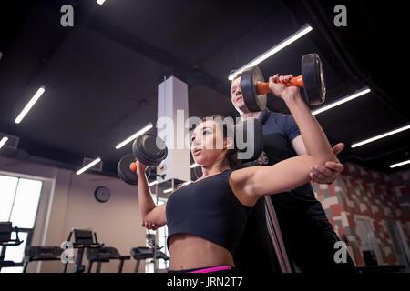 Femme Homme sport entraîneur personnel avec l'équipement de formation de poids Banque D'Images