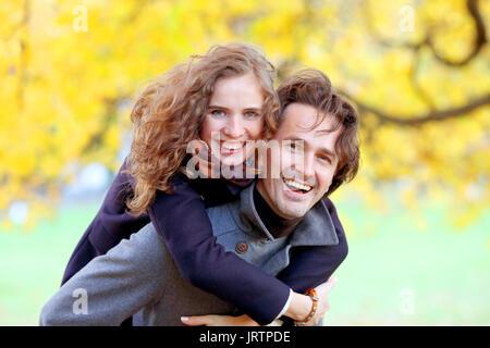 L'amour, les relations, la saison et les gens concept - happy young couple having fun in autumn park piggyback ride Banque D'Images