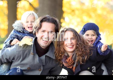 Donner aux enfants les parents piggyback ride à l'automne jaune park Banque D'Images