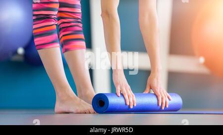 Jeune femme bleu pliable tapis de sol fitness yoga ou après l'entraînement. Vie saine, garder l'ajustement concept.