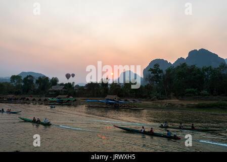 Beaucoup de bateaux sur la rivière Nam Song avec des touristes de voir l'incroyable coucher de Vang Vieng sur les Banque D'Images