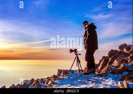 Photographe professionnel prend des photos avec l'appareil photo sur trépied sur piton rocheux au coucher du soleil. Banque D'Images