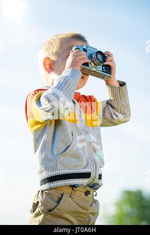 Petit garçon avec un ancien appareil photo shooting en extérieur. Banque D'Images