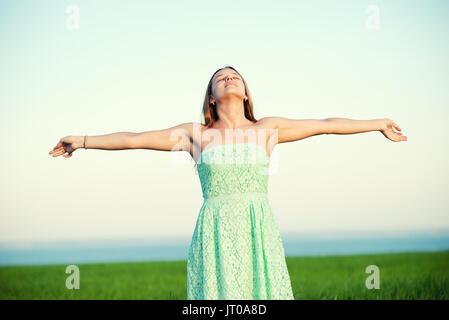 Bonheur femme rester extérieur sous la lumière du soleil de coucher du soleil Banque D'Images