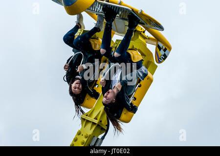 Deux jeunes femmes bénéficiant d'un parc d'rouler sous la pluie sur la jetée de Brighton, Brighton, East Sussex, Banque D'Images