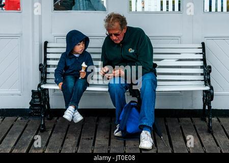 Un homme et un petit garçon assis sur un banc à l'abri de la pluie sur la jetée de Brighton, Brighton, Sussex, UK Banque D'Images