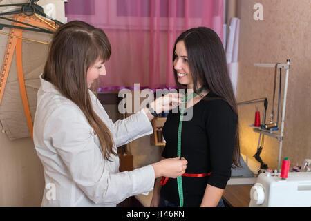Couturière prend des mesures d'aide client heureux bande dans l'atelier. Couture passe-temps comme une petite entreprise Banque D'Images