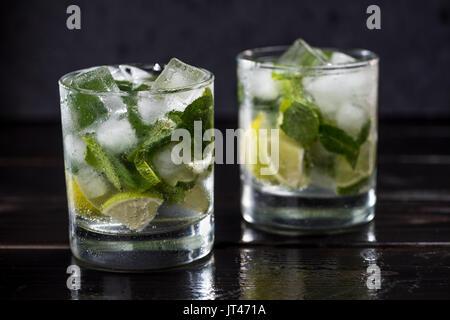 Vue rapprochée de mojito cocktail dans des verres sur la table en bois sombre, des cocktails concept Banque D'Images