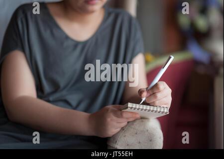De la main gauche femme écrit une idée sur petit bloc-notes tout en étant assis sur une chaise dans la chambre. Banque D'Images