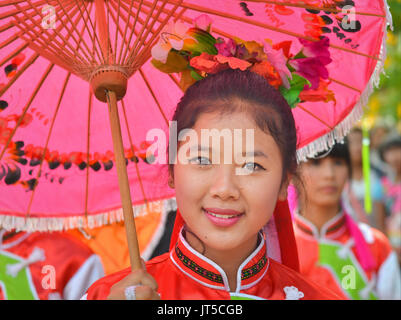 Jolie fille chinoise thaïlandaise dans une robe traditionnelle avec des sourires de parasol rouge pour l'appareil photo.
