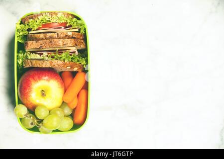 L'école verte boîte à lunch avec sandwich, pomme, raisin et carotte close up sur fond blanc. De saines habitudes Banque D'Images