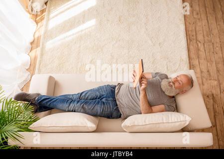 Homme barbu senior smiling and using digital tablet et lying on sofa at home Banque D'Images