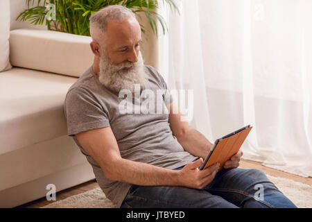 Homme barbu senior smiling and using digital tablet et assis sur le plancher à la maison Banque D'Images