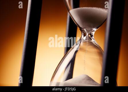 Vue rapprochée de l'ampoules en verre avec du sable qui traverse d'un sablier hourglass ou mesurer le temps de compter Banque D'Images