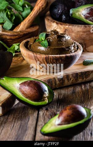 Mousse au chocolat à l'avocat de bol en bois d'olive. Bacground en bois Banque D'Images