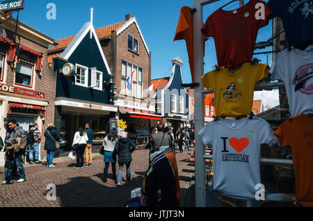 Edam, Pays-Bas - le 26 avril 2016: les touristes de marcher le long de la rue principale de Volendam avec café, Banque D'Images