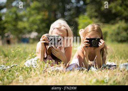Mère et fille prendre des photos lying on blanket in park.