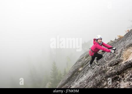 Une femme sourit d'excitation alors qu'elle remonte le metal echelons d'une Via Ferrata à Squamish.