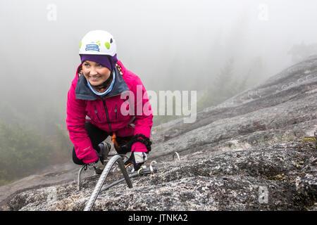 Une femme atteint pour le métal retenti alors que l'escalade la Via Ferrata à Squamish, en Colombie-Britannique.
