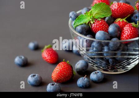 Bol en verre remplis de produits frais bio bleuets, mûres, framboises et fraises garnie de feuilles de menthe Banque D'Images