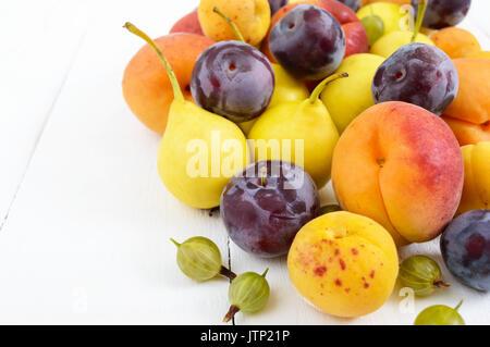 Un tas de juicy fruits d'été sur fond de bois blanc (prunes, abricots, poires). La récolte du jardin. Une source Banque D'Images