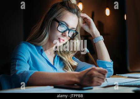 Blonde fatiguée caucasian student en lunettes d'écrire quelque chose avec un crayon et de l'étude jusqu'à la fin Banque D'Images