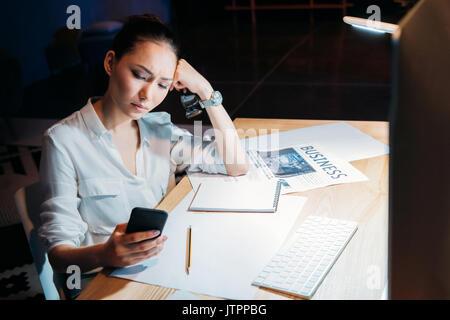 Les jeunes fatigué asian businesswoman holding eyeglasses and using smartphone, travailler tard au bureau Banque D'Images