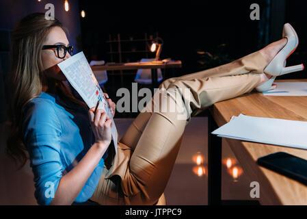 Young businesswoman holding newspaper lunettes dans tout en travaillant à la fin de l'office de tourisme Banque D'Images