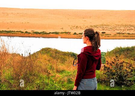 Une jeune femme regarde de Weymouth, sur la lagune, à la flotte au-delà de la plage de Chesil Banque D'Images