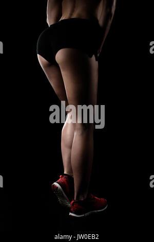 La sportive de posing in sportswear et montrant ses jambes musclées isolated on black Banque D'Images