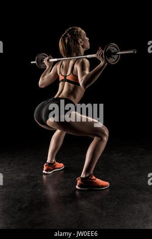La jeune femme dans les vêtements de sport et à la suite d'haltères de levage Banque D'Images