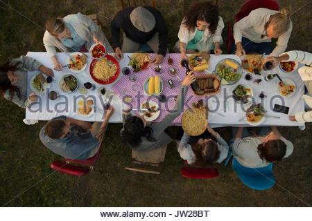 Vue de dessus les amis boire et manger au dîner garden party Banque D'Images
