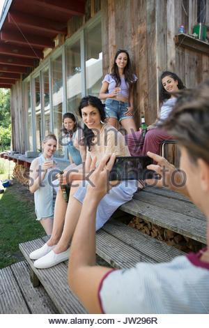 Femme avec téléphone appareil photo photographier les amis de boire une bière sur la terrasse de la cabine Banque D'Images