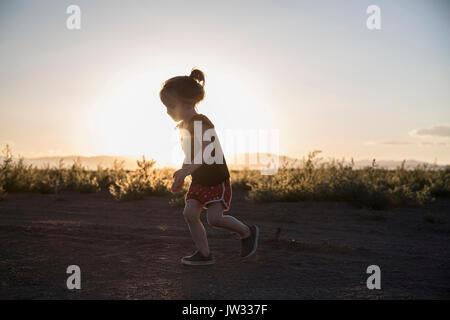 USA, Colorado, Little girl (4-5) s'exécutant sur route de terre au coucher du soleil Banque D'Images