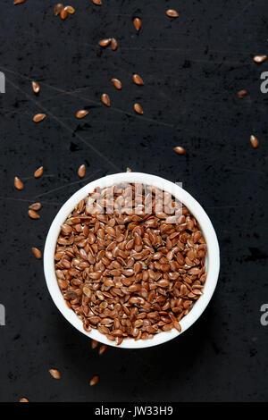 Bol rempli de graines de lin sur fond noir Banque D'Images