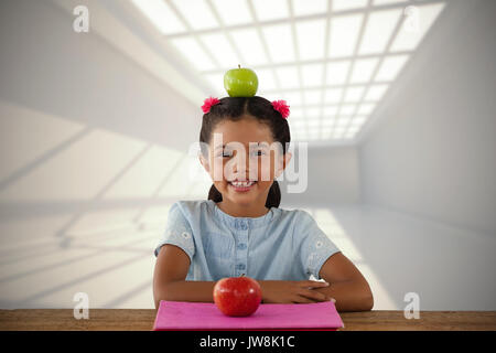 Smiling girl avec Granny Smith apple sur tête contre chambre avec des fenêtres en toiture Banque D'Images