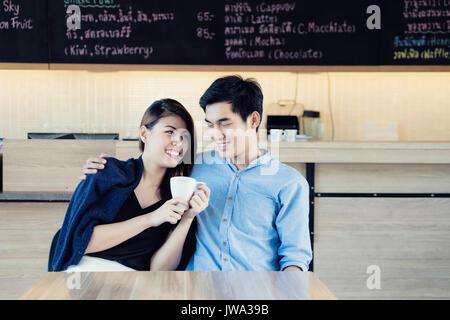 Rencontres dans un café. Belle asiatique amant couple sitting in a cafe bénéficiant dans le café et la conversation. Banque D'Images