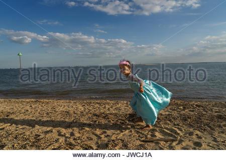 Une fillette de trois ans, vêtu d'un costume de princesse, sur la plage. Banque D'Images