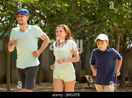 La famille sportive avec des fils d'exécution en journée d'été au parc Banque D'Images