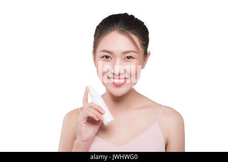 Beau modèle montrant l'application de crème cosmétique traitement sur son visage