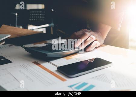 Finances comptabilité,homme,l'investissement l'analyse des graphiques avec la technologie portable calculatrice Banque D'Images