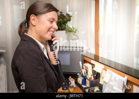 Réceptionniste professionnelle répondant à l'appel téléphonique Banque D'Images