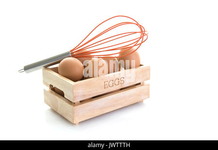 Oeufs dans une boîte en bois avec un fouet l'oeuf orange sur fond blanc Banque D'Images