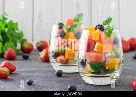 Salade de fruits frais et sain en verre transparent sur fond sombre.. De délicieux repas d'été: fraises, bleuets, Banque D'Images