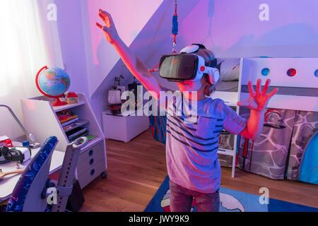 Petit garçon, 7 ans, joue un jeu d'ordinateur 3-D, avec un casque de réalité virtuelle, dans sa chambre d'enfants, Banque D'Images