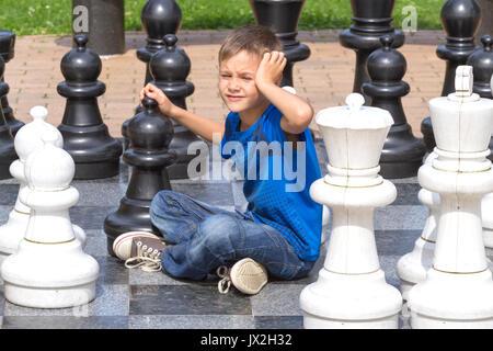Jeu d'échecs géant avec pièce. Garçon jouant sur jeu stratégique une carte noir et blanc