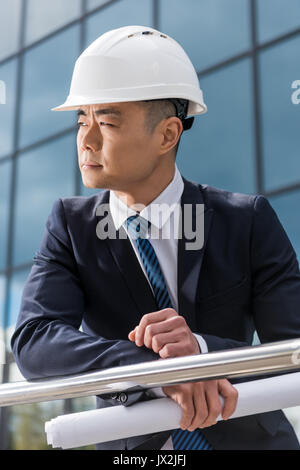 Portrait d'architecte professionnel in hard hat holding blueprint